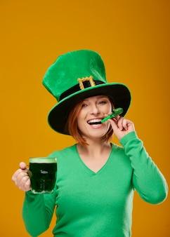 Vrouw met een feesthoornblazer en een bierglas