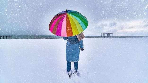 Vrouw met een felgekleurde paraplu staat in een sneeuwjacht