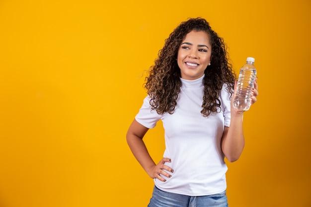 Vrouw met een fles water op gele achtergrond. drink water!