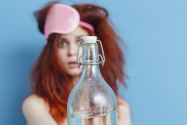 Vrouw met een fles wodka na een feestje, kater, alcoholisme