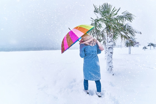 Vrouw met een gekleurde paraplu onder groenblijvende palmbomen bedekt met sneeuw