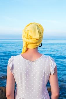 Vrouw met een gele sjaal die haar haarloze hoofd bedekt en de horizon van de zee overweegt