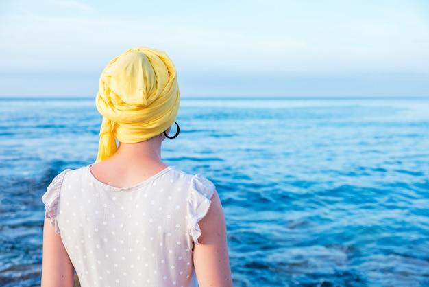 Vrouw met een gele sjaal die van het uitzicht op zee geniet