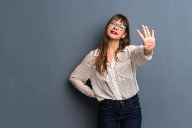 Vrouw met een gelukkige bril en vier met vingers tellen
