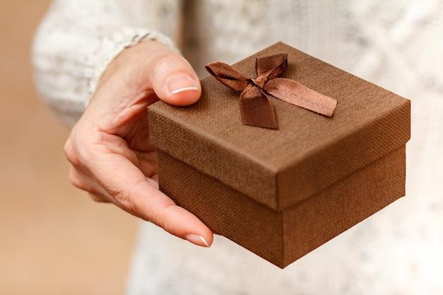 Vrouw met een geschenkdoos in haar hand. ondiepe scherptediepte, selectieve focus op de doos. concept van het geven van een cadeau op vakantie of verjaardag.