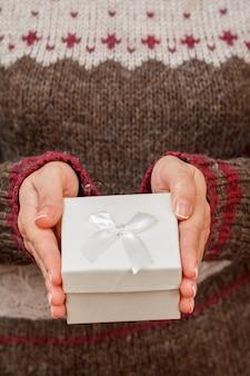 Vrouw met een geschenkdoos in haar handen. ondiepe scherptediepte, selectieve focus op de doos. concept van het geven van een cadeau op vakantie of verjaardag.
