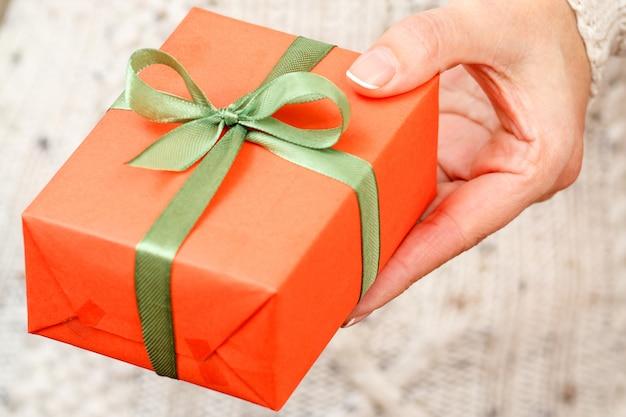 Vrouw met een geschenkdoos vastgebonden met een groen lint in haar hand. ondiepe scherptediepte, selectieve focus op de doos. concept van het geven van een cadeau op vakantie of verjaardag.