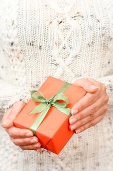 Vrouw met een geschenkdoos vastgebonden met een groen lint in haar handen. ondiepe scherptediepte, selectieve focus op de doos. concept van het geven van een cadeau op vakantie of verjaardag.