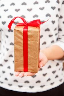 Vrouw met een geschenkdoos vastgebonden met een rood lint in haar hand. ondiepe scherptediepte, selectieve focus op de doos. concept van het geven van een cadeau op vakantie of verjaardag.