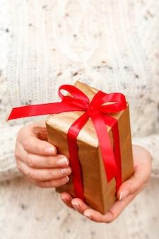 Vrouw met een geschenkdoos vastgebonden met een rood lint in haar handen. ondiepe scherptediepte, selectieve focus op de doos. concept van het geven van een cadeau op vakantie of verjaardag.