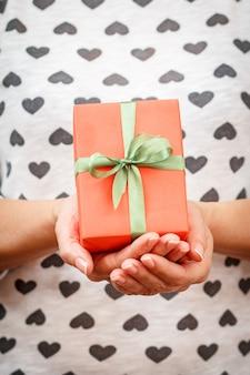 Vrouw met een geschenkdoos vastgebonden met een rood lint in haar handen. ondiepe scherptediepte, selectieve focus op de doos. concept van het geven van een cadeau op valentijnsdag of verjaardag.