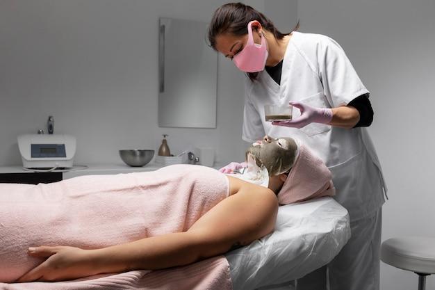 Vrouw met een gezichtsbehandeling in de schoonheidssalon