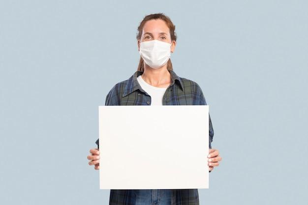 Vrouw met een gezichtsmasker die een blanco vasthoudt