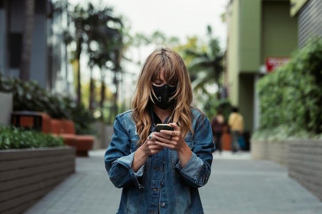 Vrouw met een gezichtsmasker die een telefoon gebruikt tijdens de uitbraak van het coronavirus