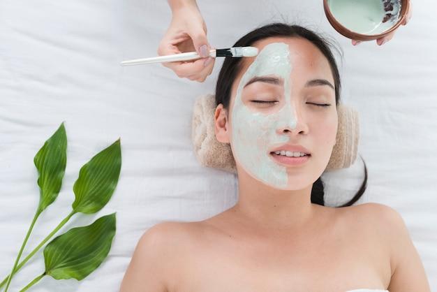 Vrouw met een gezichtsmasker in een spa