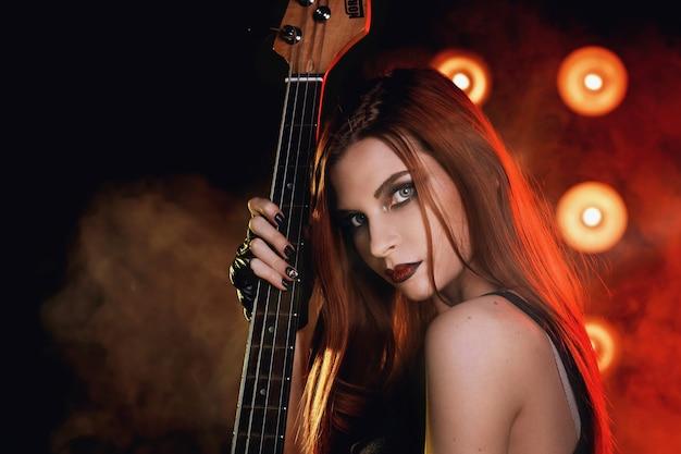 Vrouw met een gitaar in handen op het podium zingt een lied in rockstijl