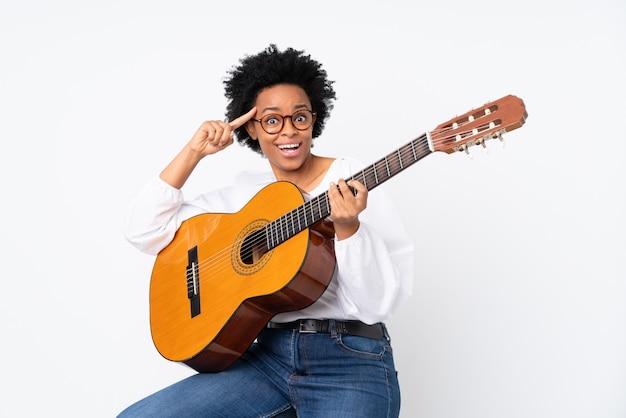 Vrouw met een gitaar over witte muur
