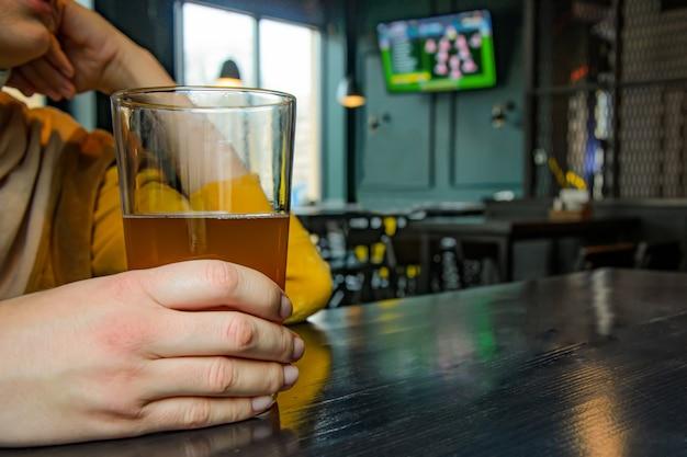 Vrouw met een glas licht bier kijken naar voetbalwedstrijd in pub