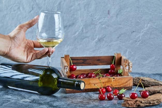 Vrouw met een glas witte wijn en houten kist met kersen op blauwe ondergrond