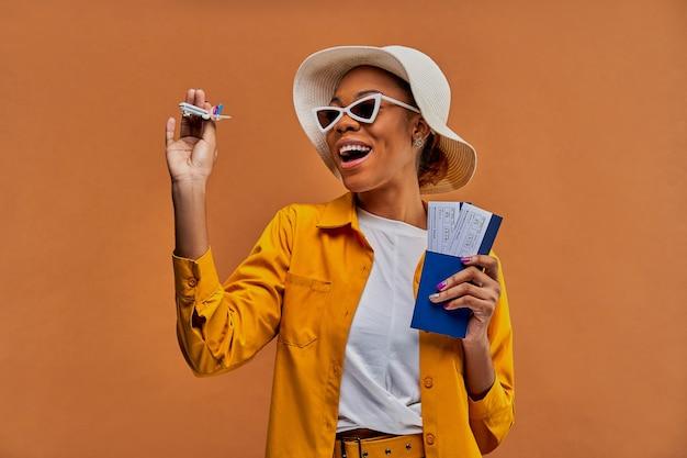 Vrouw met een glimlach in een witte hoed in een witte zonnebril in geel overhemd met een speelgoedvliegtuig met een paspoort met kaartjes in handen. reis concept