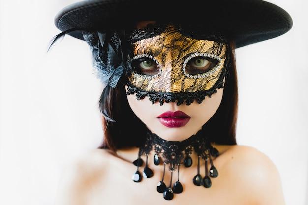 Vrouw met een gouden venetiaans masker en een zwarte hoed op een witte achtergrond