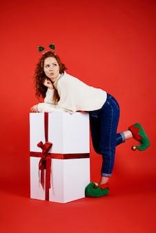 Vrouw met een groot kerstcadeau kijken naar kopie ruimte