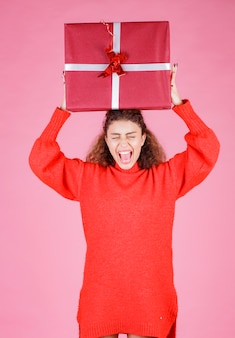 Vrouw met een grote geschenkdoos boven haar hoofd.