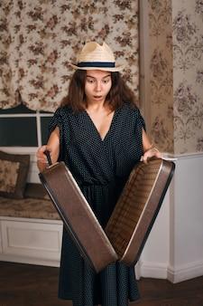 Vrouw met een halfopen koffer in haar handen.