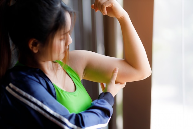 Vrouw met een hand met overtollig vet. concept van ongezonde levensstijl.