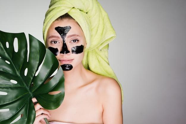 Vrouw met een handdoek op haar hoofd bracht een masker aan op probleemgebieden van de huid