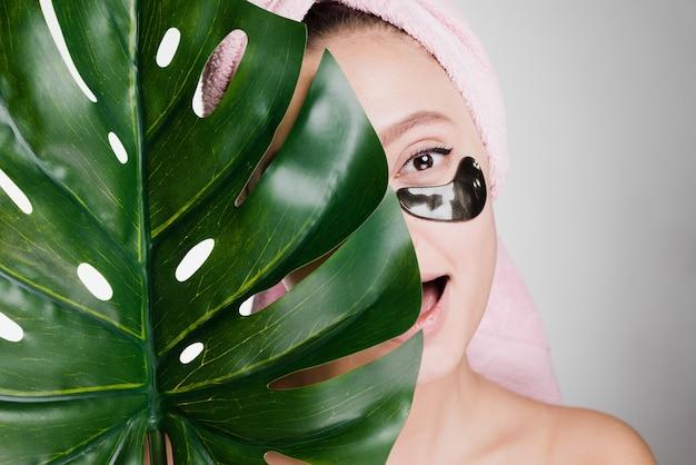 Vrouw met een handdoek op haar hoofd heeft haar ooglapjes gepatcht