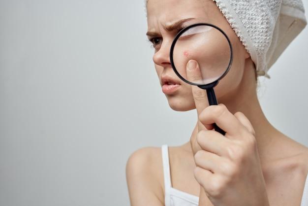 Vrouw met een handdoek op haar hoofd houdt een vergrootglas dichtbij gezicht