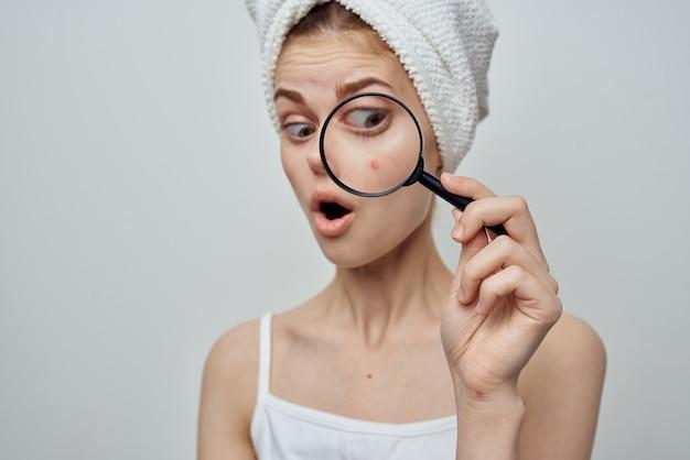 Vrouw met een handdoek op haar hoofd vergroot puistjeshuidproblemen door een vergrootglas