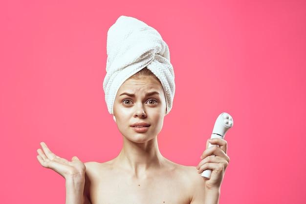 Vrouw met een handdoek op het hoofd die de close-up van de huidtherapie schoonmaakt