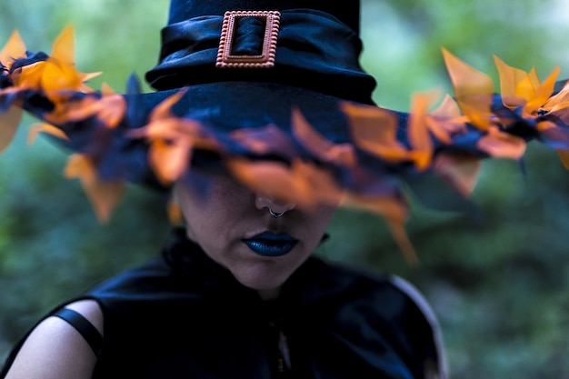 Vrouw met een heksenmake-up en kostuum met een versierde hoed gevangen in een bos