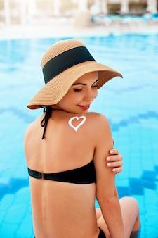 Vrouw met een hoed aan de rand van een zwembad die zonnebrandcrème met hartvorm op een gebruinde schouder toepast.