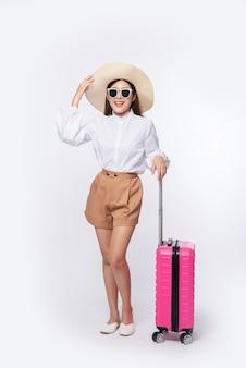Vrouw met een hoed, bril en handvatten van koffers om te reizen