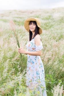 Vrouw met een hoed, gekleed in een witte jurk, staande in het midden van het gras met prachtige witte bloemen met een ontspannen en vrolijke sfeer.