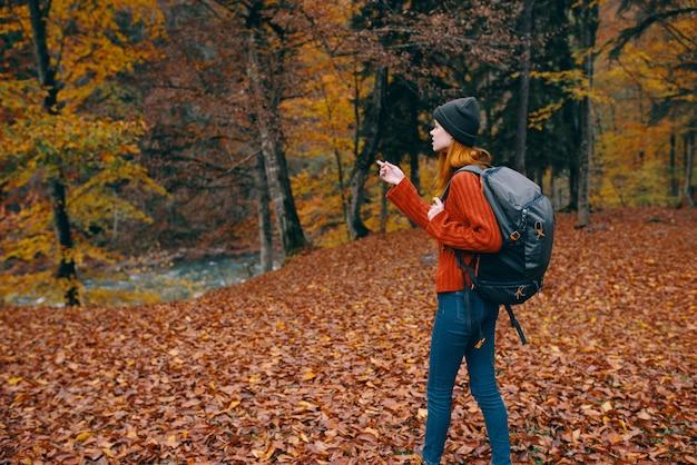 Vrouw met een hoed in een rode trui en spijkerbroek loopt in het park met een rugzak op haar rugreis