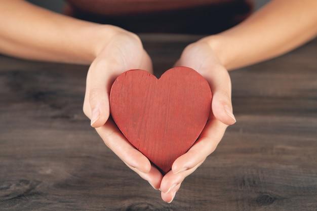 Vrouw met een houten hart in haar handen