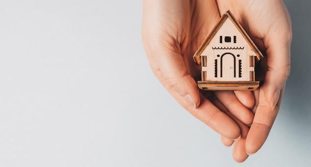 Vrouw met een houten huis met haar handen met de zon op een lichtblauwe achtergrond. lief huis