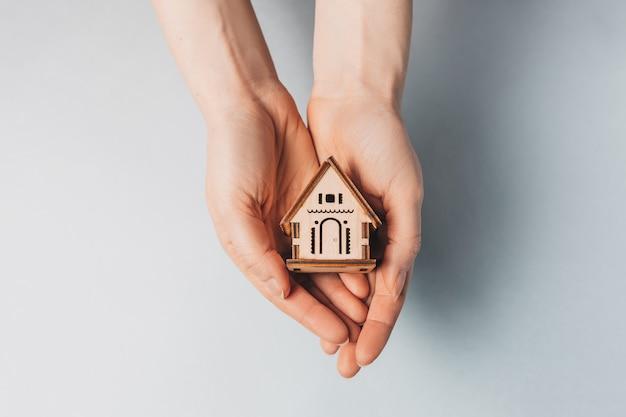 Vrouw met een houten huis met haar handen met de zon op een lichtblauwe ruimte