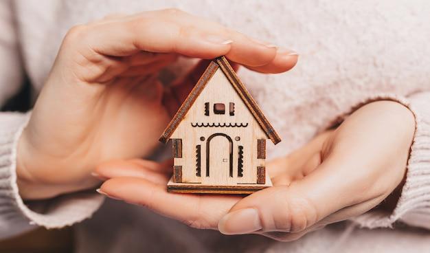 Vrouw met een houten huis met haar handen met de zon op een lichtroze ruimte