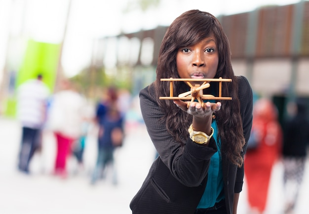 Vrouw met een houten vliegtuig in haar hand