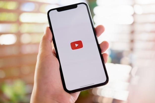 Vrouw met een iphone x of iphone 10 met sociale internetdienst youtube op het scherm