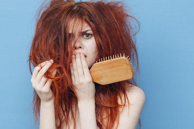 Vrouw met een kam die haar slordige haar probeert te borstelen