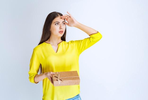 Vrouw met een kartonnen geschenkdoos en ziet er in beslag genomen of attent uit.