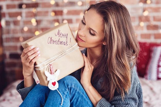 Vrouw met een kerstcadeautje in bed zitten