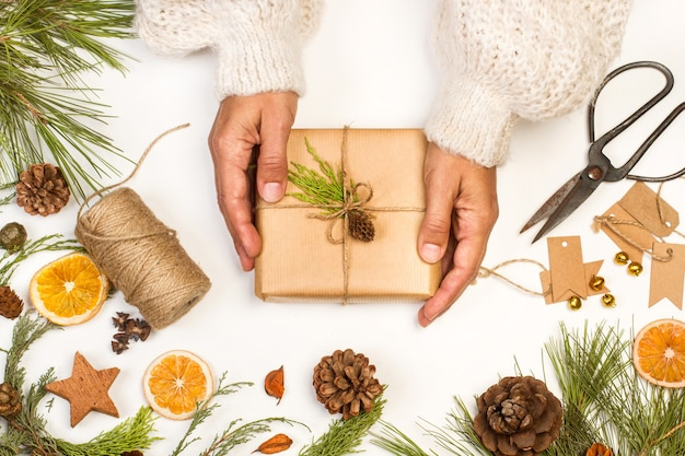 Vrouw met een kerstpakket op een witte tafel