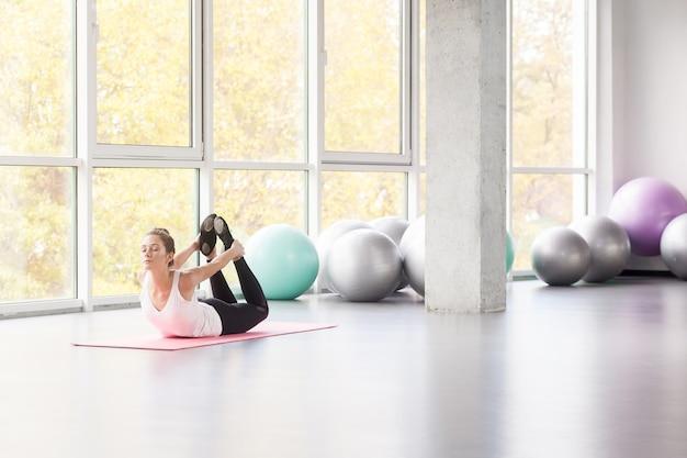 Vrouw met een kleine glimlach die yoga, booghouding, yoga doet. dhanurä sana. studio opname